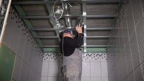 Furo de broca do trabalhador para fixar perfis do teto Poeira que cai no homem do trabalhador manual vídeos de arquivo