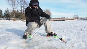 Furo de brocas do pescador no fim do gelo acima da vista, pesca desportiva no inverno video estoque