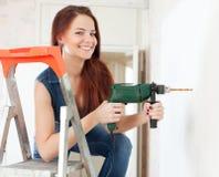 Furo de brocas feliz da mulher na parede imagem de stock