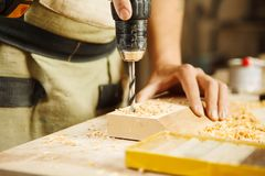 Furo de perfuração disponivel da broca da perfuração de madeira na barra de madeira Fotos de Stock