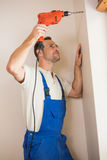 Furo de perfuração do trabalhador da construção na parede Fotos de Stock Royalty Free