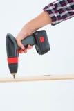 Furo de perfuração masculino do carpinteiro na madeira Foto de Stock
