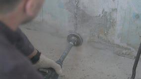Furo do concreto com uma coroa redonda da construção o trabalhador fura uma parede com um perfurador vídeo de movimento lento filme