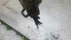 Furo do concreto na estrada com brocas fotos de stock