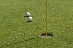 Furo e bolas de golfe na parte traseira do verde Foto de Stock Royalty Free