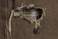 Furo em calças de brim gastas Imagem de Stock