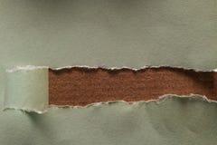 Furo longo áspero na folha do papel vazio com o rasgo de papel envolvido Fundo de madeira da tabela Janela arrebatada madeira fotografia de stock