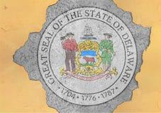 Furo rachado com sumário da bandeira do selo de Delaware do estado de E.U. na fachada fotografia de stock