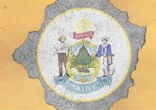 Furo rachado com sumário da bandeira do selo de Maine do estado de E.U. na fachada foto de stock