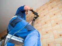 Furos de brocas do trabalhador na parede com um perfurador Imagem de Stock Royalty Free