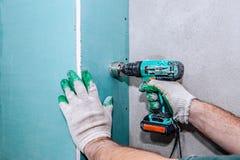 Furos de brocas de um trabalhador em uma parede da placa de gesso com uma broca elétrica Reparo na casa foto de stock royalty free