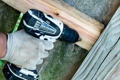 Furos de perfuração do homem para o reparo de madeira da cerca Foto de Stock