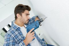 Furos de perfuração masculinos do construtor na parede no canteiro de obras Imagem de Stock Royalty Free