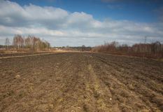 Furrows plowed field early in spring Royalty Free Stock Images