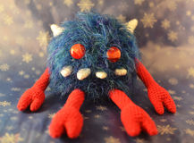 Furry Monster Crochet Toy. Fluffy monster with fur, horns and big teeth. Crochet handmade Stock Photo