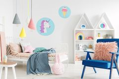 Furry pink pillow on a vibrant blue armchair in a sweet kid bedroom interior with cozy bedding and cartoon posters on white walls royalty free stock images
