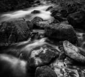 Furry Rocks BW. Slow motion river moves over mossy rocks in the Wasatch mountains in Utah USA Stock Photos