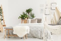 Furry rug on bench. White furry rug placed on wooden bench standing by the bed with bright bedclothes royalty free stock photography