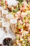Furshet Sobremesa por completo de vidrios de vino blanco chispeante con canapes y antipasti en el fondo Champán Imagen de archivo