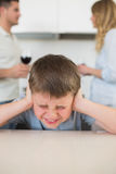 Furstrated boy covering ears while parents arguing Stock Photo