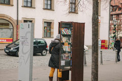 Furth, Germany, December 28, 2016: A woman chooses a book. Street public library. Education in Germany. Lifestyle. Everyday life in Europe stock photography