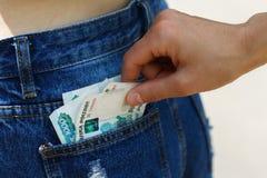 Furto di soldi dalla tasca della gente non vigilante fotografie stock