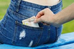 Furto di soldi dalla tasca posteriore fotografia stock libera da diritti