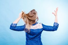 Furious woman pull hair out of head. Fury and big anger inside of people. Blonde furious woman pulling blonde hair out of head. Emotional young girl showing her Royalty Free Stock Photo