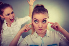 Fury girl screaming at her friend, female closing his ears Stock Photography