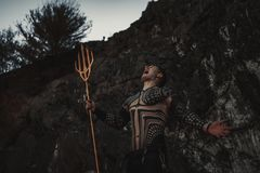 A fury man with a trident in his hands against the background of rocks. A fury man in armor and with a trident in his hands against the background of rocks stock photo