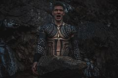 A fury man with a trident and a big stone in his hands is next to the rocks. A fury man in armor with a trident and a big stone in his hands against the royalty free stock photo