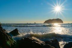 Fusée de lentille, stupéfiant au-dessus du bord côtier rocheux image stock