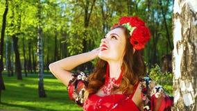 Fusée de lentille sur la jolie jeune femme dans le costume dénommé folklorique jetant un coup d'oeil du bouleau banque de vidéos