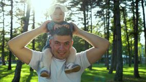 Fusée de lentille sur le père de sourire tenant sa fille d'enfant en bas âge sur des épaules dehors banque de vidéos