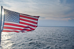 FUS Flag over water. US flag at sunset over water Royalty Free Stock Photos