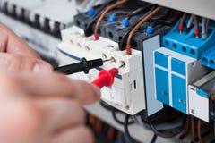 Fusebox d'esame dell'elettricista con la sonda del multimetro immagini stock