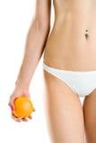 Fuselage de jeune femme et orange de fixation de main Image stock