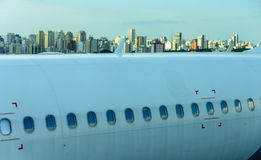 Fuselage of the narrow-body aircraft with white clouds and blue sky reflected in the portholes. At the airport on the background of high-rise modern buildings Stock Photos