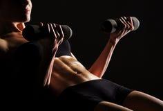 Fuselage sexy d'un jeune femme faisant la séance d'entraînement d'ABS Photographie stock