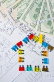 Fuses and money on construction drawings Royalty Free Stock Images