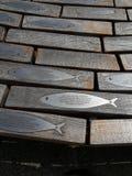 Fush plakiety umieszczać na ikonowych ławkach robić wyginający się szalunek z metal ryba jako ich backrests Seaford wschód Sussex obrazy stock