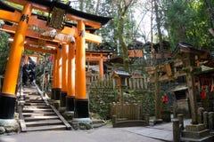 Fushimi Inari grande Torii arancio con il santuario e poca gente immagini stock