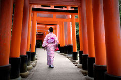 Fushimi-inari. Woman dressed in traditional japanese costume walking under tori gates at the fushimi-inari shrine, Kyoto Japan Stock Photos