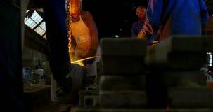 Fusión del trabajador fundida en horno en el taller 4k de la fundición almacen de video