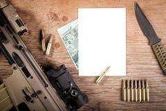 Fusil d'assaut, une carte et un papier sur la table Photos libres de droits