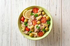 Fusilli与金枪鱼、蕃茄、橄榄和荷兰芹的意大利面制色拉在白色木背景 库存图片