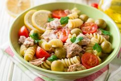 Fusilli与金枪鱼、蕃茄、橄榄和荷兰芹的意大利面制色拉在白色木背景 免版税库存照片