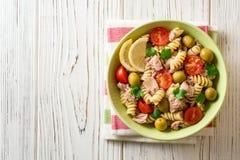 Fusilli与金枪鱼、蕃茄、橄榄和荷兰芹的意大利面制色拉在白色木背景 免版税库存图片