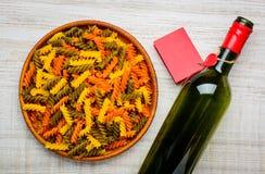 Χρωματισμένα ζυμαρικά Fusilli και κρασί μπουκαλιών Στοκ φωτογραφία με δικαίωμα ελεύθερης χρήσης
