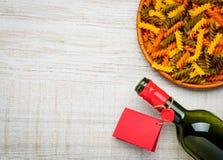 Κρασί μπουκαλιών, χρωματισμένα ζυμαρικά Fusilli και διάστημα αντιγράφων Στοκ φωτογραφία με δικαίωμα ελεύθερης χρήσης